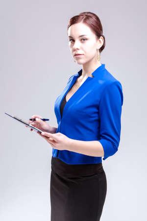 Photo pour Portrait of Caucasian Entrepreneur in Blue Jacket Posing With Notepad and Pen In Studio. Against White. Vertical Image - image libre de droit