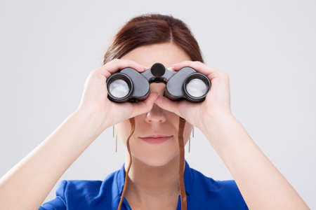 Photo pour Information Search Concepts. Caucasian Brunette Female Posing With Binoculars as a Concept of Search. Horizontal image - image libre de droit
