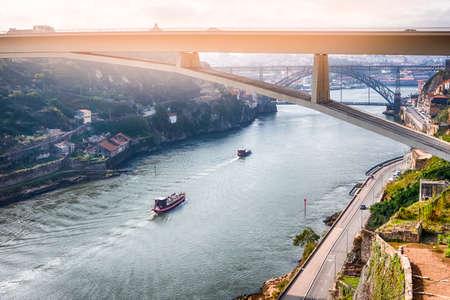 Photo pour Travel Places Ideas. Line of Tourist Boats and Porto Cityscape at Daytime with Ponte Infante D Henrique in Background in Portugal. Horizontal image Composition - image libre de droit