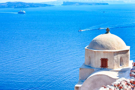 Photo for Sailing Boats Near Caldera Volcanic Slopes of Santorini Oia or Ia Village in Greece. With Traditional Pale Dome Orthodox Greek Church in Foregound. Horizontal Image - Royalty Free Image