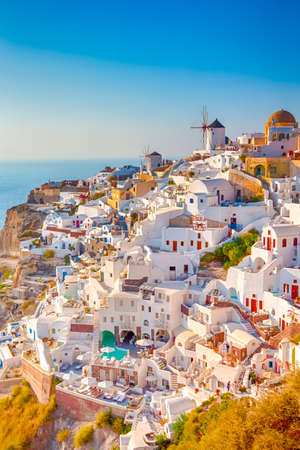 Photo for Traditional Colorful Houses and Windmills of Oia or Ia at Santorini Island at Noon. Vertical Image Orientation - Royalty Free Image