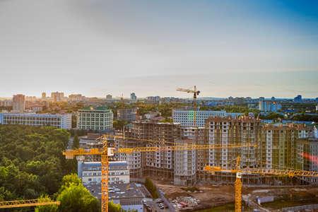 Photo pour New Construction Site with Building Cranes Against Sunny Sky. Horizontal Image Orientation - image libre de droit
