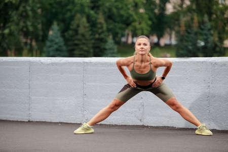 Photo pour Sport Ideas. Caucasian Female Runner Doing Stretching Exercises Outdoor. Horizontal Image - image libre de droit
