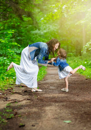Photo pour Caucasian Mother with Her Daughter Walking Together in Green Summer Forest Outdoors. Horizontal image Orientation - image libre de droit