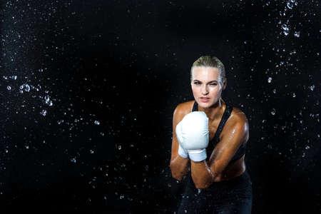 Photo pour Portrait of Professional Active Female Boxer  Posing with White Gloves in Aqua Studio Against Black Background. Horizontal Shoot - image libre de droit