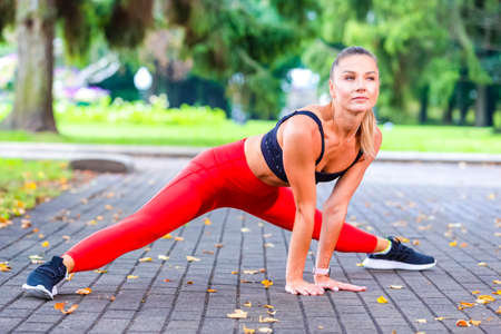 Photo pour Sexy Caucasian Female Runner During Forward Stretching Body Exercises Outdoors At Daytime. Horizontal Image - image libre de droit