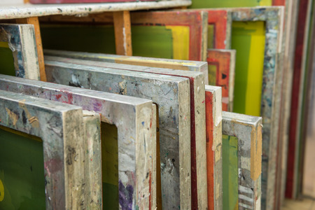 Photo for Silk screen printing screens stored in a wooden rack ready for printing. - Royalty Free Image