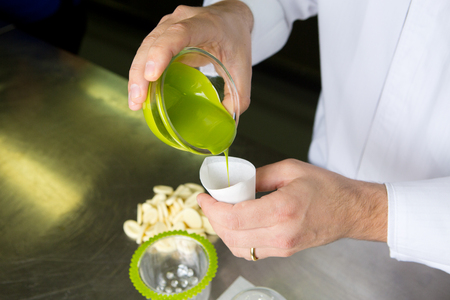 melted white creamy chocolate that has been dyed a lime green colour, being poured into an icing piper,  in preparation for decorating a mango and lime desert.