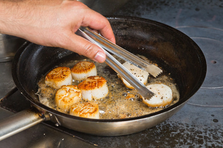 Delicious pan seared organic scallops being flipped over and seared in a metal cooking pan on the hob. Presented professionally and shot with a shallow depth of field.