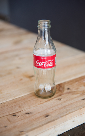 10/10/2018 An empty vintage glass coca cola coke bottle isolated against  s rustic background.