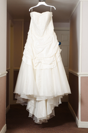 Foto de A beautiful cream and clean Wedding dress Hanging in the hall of a hotel room. Wedding love fashion and celebration. - Imagen libre de derechos