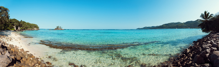 A stunning wide panoramic large format photograph of The stunning Anse royal beach in the seychelles, island of mahe. Paradise and beautiful blue sky.