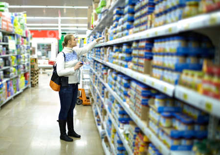 Young woman is choosing food for her child at the food store  Wide shot, shallow dof