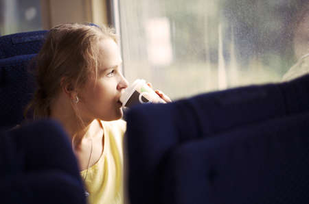 Pensive blond young woman drinking coffee and looking out the window while traveling by train