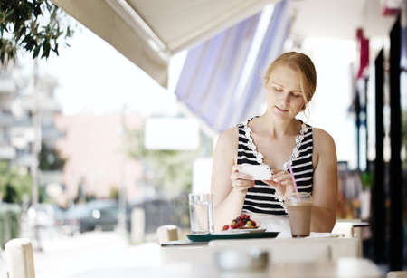 Attractive woman taking picture of a pastry on her smart phone as she sits at a table at an open-air restaurant enjoying refreshments