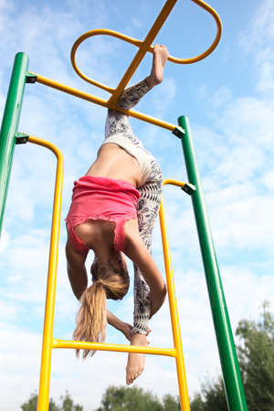Athletic young blond gymnast working out on colourful metal bars in an outdoor playground hanging gracefully from one leg while stretching down with her other foot against a cloudy blue sky