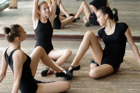 Three ballet dancers on the floor with their toes touching