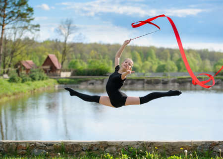 Young rhythmic gymnast doing split jump during ribbon exercises.