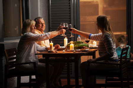 Foto de Family dinner outdoor in the backyard in quiet evening. Young woman and senior parents toasting with wine while child playing games - Imagen libre de derechos