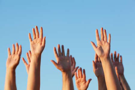 Photo for Group of people raising their hands in the air against a clear sunny blue sky in a conceptual image with copy space - Royalty Free Image