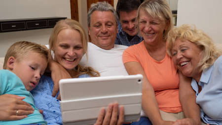 Photo pour A big family is watching something funny on a pad, close side by side - image libre de droit