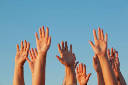 Photo pour Ten raised up sunlit adult hands on the blue sky background - image libre de droit