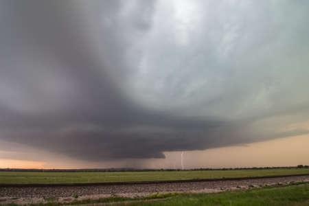 Supercell thunderstorm with lightning strike near sunset.