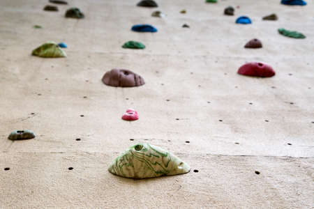shallow depth of field looking up a climbing wall focused on the foot grip closest to the camera