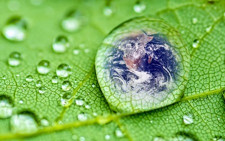 planet earth inside a raindrop closeup on a green leaf (Elements of this image furnished by NASA )
