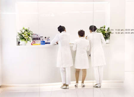UDON THANI, THAILAND JULY 18 2012: Three technicians stand inside the reception area of a skin care clinic in Udon Thani.