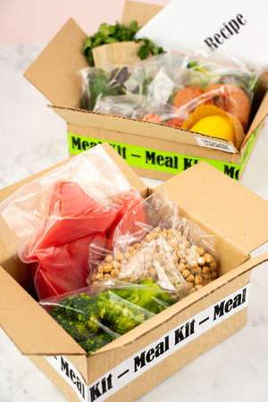 Photo for Online Home Food Delivery. Craft Box with packed tuna, shrimp, vegetables and recipe card on a kitchen background. Food delivery services during coronavirus pandemic and social distancing. - Royalty Free Image