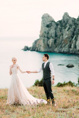 Photo pour Beautiful bride and groom hug each other tender standing on the golden hill near sea - image libre de droit
