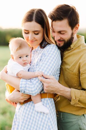Foto de portrait of a happy young family, where mom and dad hug each other, holding their little child between them in the rays of the sunset, sun - Imagen libre de derechos