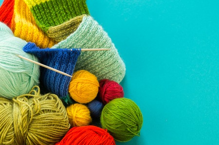 Photo pour Knitting a rainbow scarf and hat. Basket with balls of wool, knitting needles. Blue background. Favorite work is a hobby. - image libre de droit