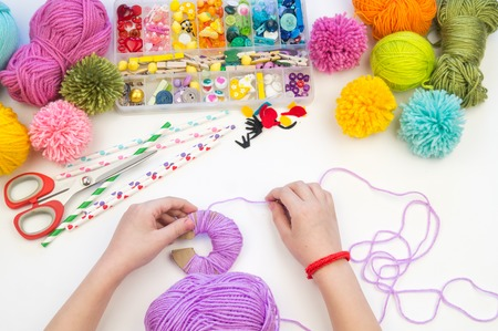 Photo pour The child is engaged in a favorite hobby. The kid makes a pom-pom from a woolen thread monster. Holiday toy gift. Creativity with children. School kindergarten. Material for crafts. - image libre de droit
