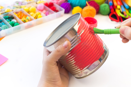 Photo pour child makes a hand-made unicorn out of a tin can. Rainbow hair Favorite hobby toy. Material for creativity and tool. White background. - image libre de droit