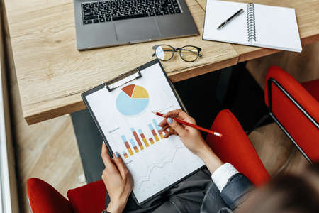 Photo pour Business woman checks charts and refreshes financial progress. The girl analyzes the business model in the workplace. - image libre de droit