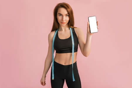 Foto per Fitness girl smiling and holding a phone with a mockup and posing hold measure tape in black sportswear on a pink background. Slim woman with a beautiful athletic body and tanned skin - Immagine Royalty Free