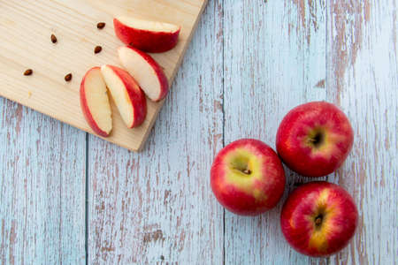 Organic ripe apples on a wooden table and apple slices on wooden board. Fresh cut apple healthy snack. Cooking ingredients. Harvest.の写真素材