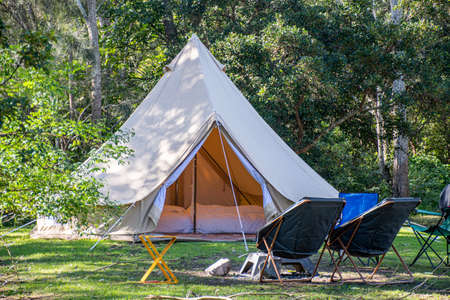 Foto de Glamping camping teepee tent and chairs at the campsite. - Imagen libre de derechos