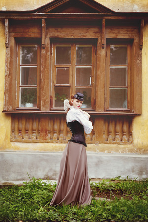 Beautiful redhair woman in vintage clothes standing near old ancient house with wooden window. Toned in warm vintage colors.の写真素材