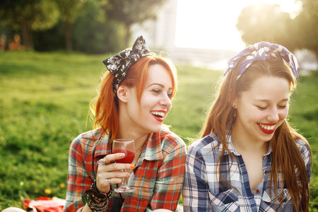 Foto de Two Young Happy Girls in Pin-Up Style on Picnic, Laughing, Drinking Wine, Having Fun. Selective Focus. - Imagen libre de derechos