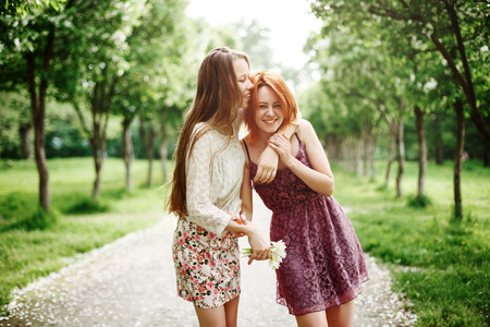 Two Young Happy Girls Having Fun in the Summer Park. Best Friends Laughing and Embracing.