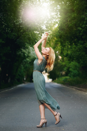 Wonderful Young Woman Dancing on the Road Alone in Summer Evening. Femininity Concept.