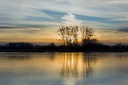 Photo pour A frozen lake, trees and blown clouds on an evening sky - image libre de droit