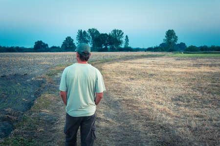 Photo pour Male farmer looks at dry farmland, summer view - image libre de droit
