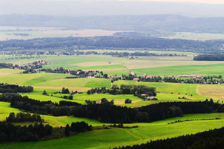 Misty valley of Broumovsko in Czech Republic with fields and green meadows. Vast panorama of Viznov village in the Sudetes Mountains.