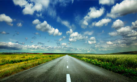 Photo pour image of wide open prairie with a paved highway stretching out as far as the eye can see with beautiful small green hills under a bright blue sky in the summer time - image libre de droit
