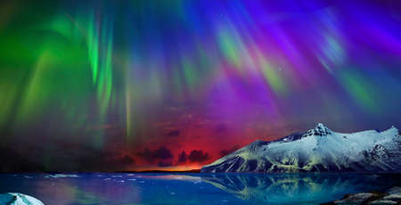 Photo pour Gorgeous, unreal beautiful night view of the reflection of the northern lights in the water of the ocean and snow-capped mountains. Night Northern Lights is just an amazing sight. - image libre de droit