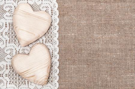 Photo pour Burlap background with white lacy cloth and wooden hearts  - image libre de droit